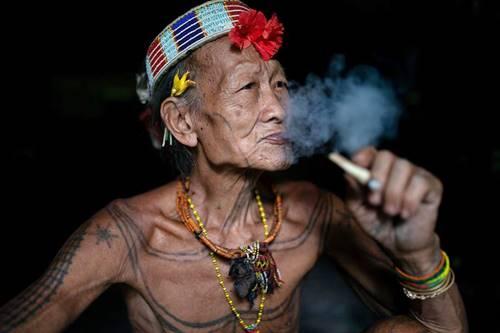Seorang kakek dari suku mentawai mentato tubuhnya dengan tati