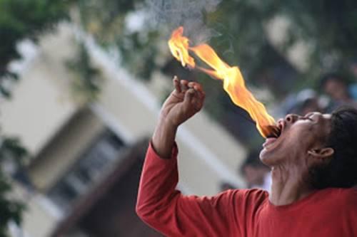 Seorang Pria yang mempraktekan tradisi debus memakan Api