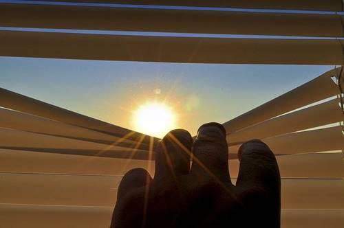 menatap sinar Matahari dari jendela