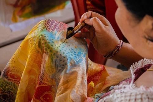 seorang wanita sedang membuat titik titik pada kain